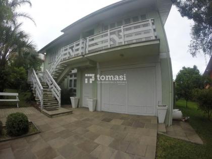 TOMASI Imóveis VENDE Casa semimobiliada com 04 dormitórios, 03 banheiros sendo 01 com banheira, sala de estar, lavabo, cozinha com dispensa, dependências para empregada, área de lazer com churrasqueira, jardim e garagem para dois veículos. Localizada no b