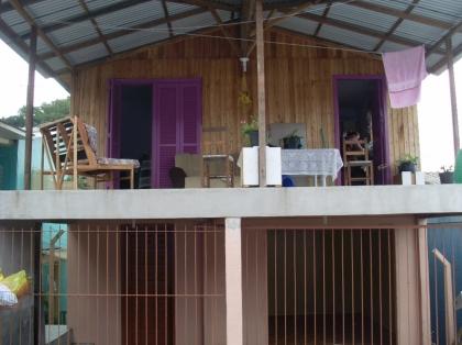 Casa de madeira com dois dormitórios, sala, cozinha, banheiro, área de serviço. Parte inferior de alvenaria.